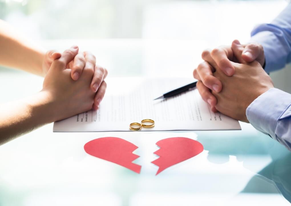 een vrouw doet haar trouwring af als onderdeel van een echtscheidingsprocedure